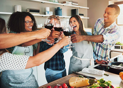 Friends at a Super Bowl party toast with wine in the kitchen