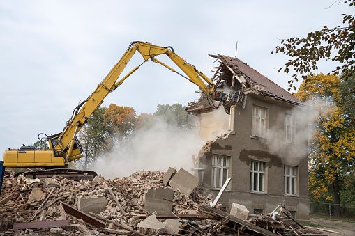 excavator demolished damaged house after an earthquake