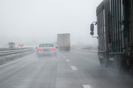 Heavy rainfall drenches a Northwest highway, limiting visibilty, which requires headlights