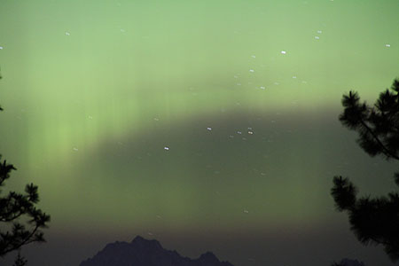 Northern lights create a green pulsating curtain over Mt. Stuart