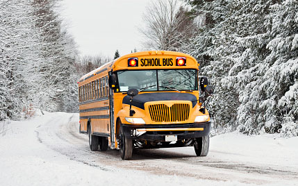 A school bus carrying a basketball team to a game travels many miles over snowy roads