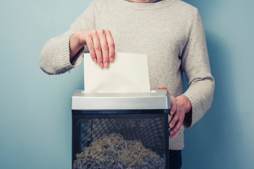 person inserting paper into shredder