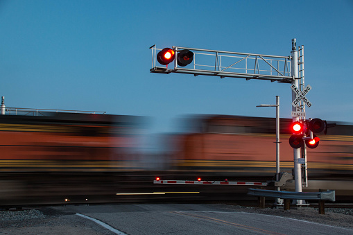 train crossing road with red lights barricade